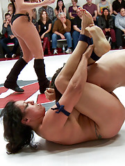 Each team takes advantage of the opposing rookie. Sasha and Ella are both trapped on the mats getting finger fucked to frustration.