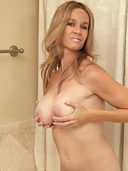 Totally Tabitha plays with her big boobs and bald pussy in the tub