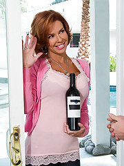 Veronica Avluv drops by her neighbors home and brings by a bottle of wine to welcome him to the neighborhood. Of course, she