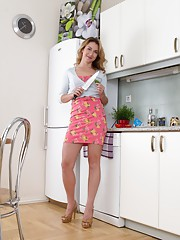 Melisa is a sexy Latvian petite blonde who is wearing a sexy floral dress in the kitchen. She slowly strips naked and gets naked on the counter. She shows off her hairy pussy and rubs her hairy lips.